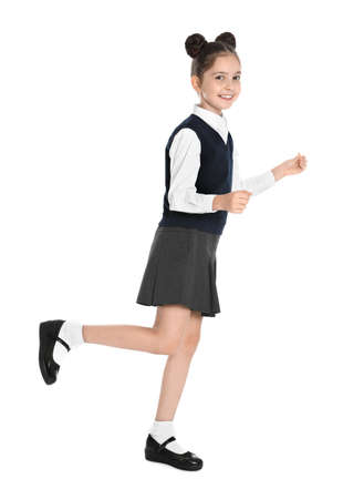 Happy girl in school uniform walking on white background