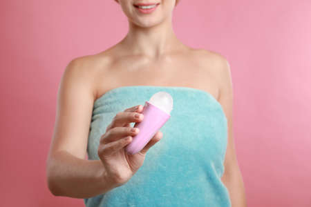 Young woman holding deodorant on pink background, closeup. Mockup for design