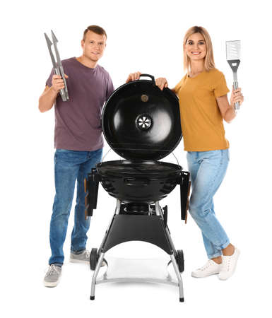 Happy couple with barbecue grill and utensils on white background Imagens