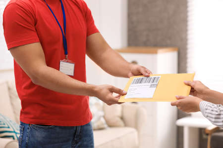 Woman receiving padded envelope from courier at home, closeup Banque d'images
