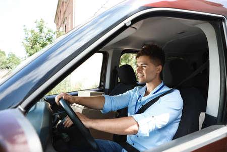 Jeune coursier avec des colis en voiture de livraison
