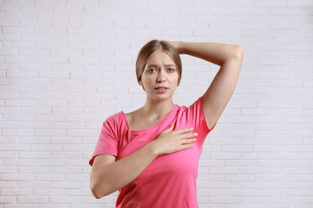 Young woman with sweat stain on her clothes against brick wall. Using deodorant