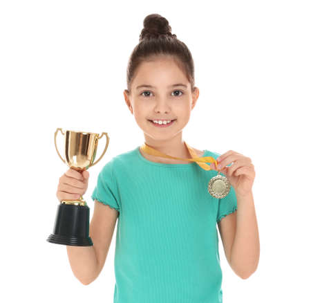 Happy girl with golden winning cup and medal isolated on white Archivio Fotografico - 129709688