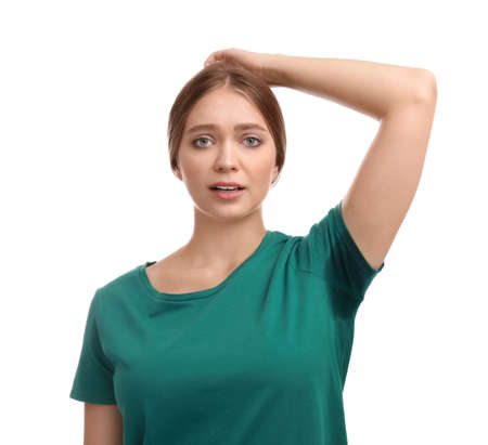 Young woman with sweat stain on her clothes against white background. Using deodorant 写真素材