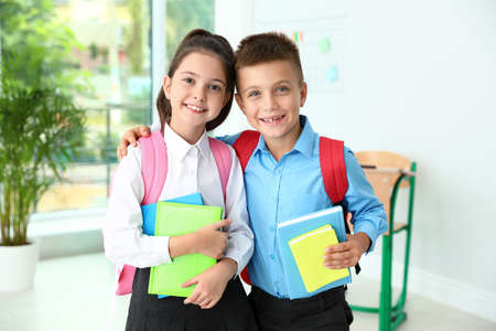 Cute little children with backpacks and school stationery in classroom Archivio Fotografico
