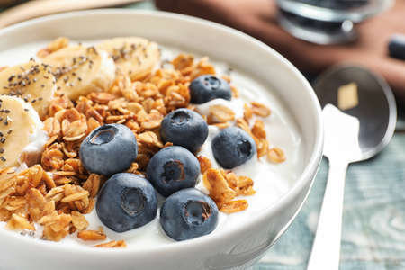 Bowl of yogurt with blueberries, banana and oatmeal on wooden table, closeup