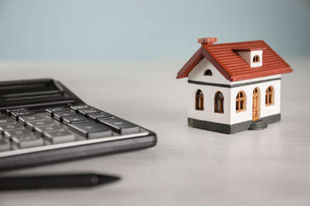 Calculator, house model and pen on light table. Real estate agents workplace Stock Photo