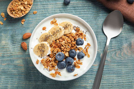 Bowl of yogurt with blueberries, banana and oatmeal on color wooden table, flat lay 写真素材