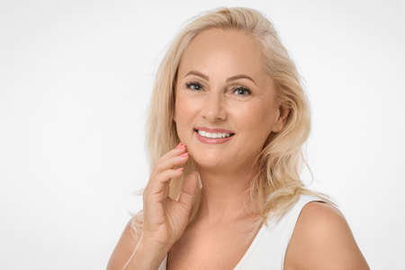 Portrait of beautiful mature woman with perfect skin on white background