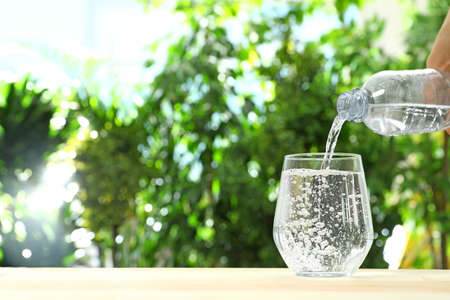 Pouring water from bottle into glass against blurred background, space for text. Refreshing drink