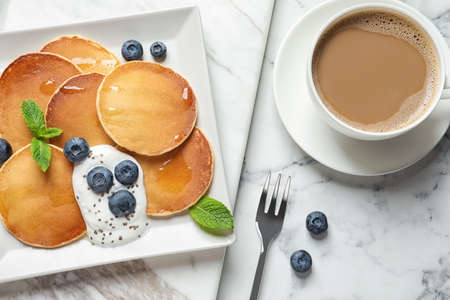 Plate of tasty pancakes with blueberries, sauce and mint on white marble table, flat lay Standard-Bild