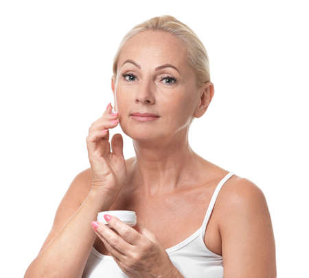 Portrait of beautiful mature woman with perfect skin holding jar of cream on white background 스톡 콘텐츠