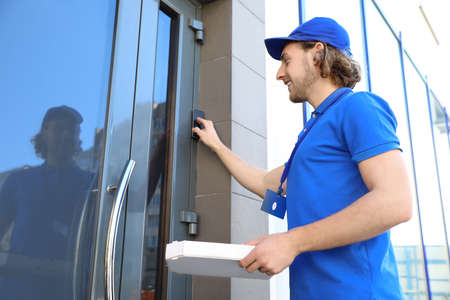Male courier with pizza ringing in doorbell at entrance. Food delivery service
