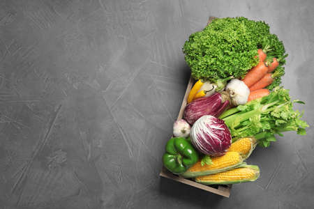 Crate with fresh vegetables on grey table, top view. Space for text