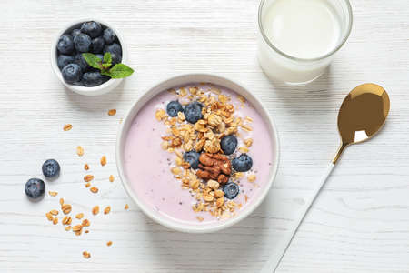 Bowl of tasty oatmeal with blueberries and yogurt on white wooden table, flat lay