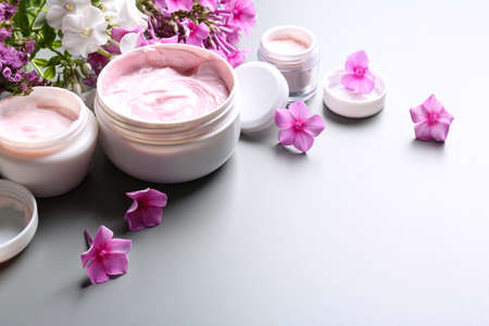 Jars of body cream and flowers on grey background. Space for text