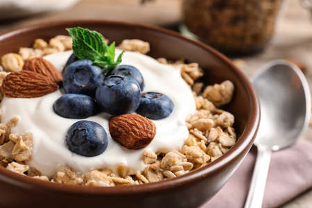Bowl of tasty oatmeal with blueberries and yogurt on table, closeup