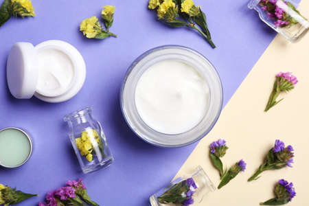 Flat lay composition with jars of body cream on color background