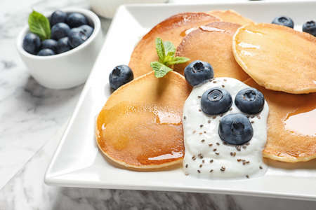 Plate of tasty pancakes with blueberries, sauce and mint on marble table, closeup 免版税图像