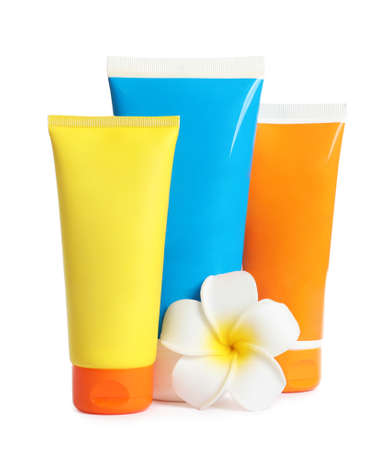 Tubes with sunscreen cream and flower on white background. Cosmetic products