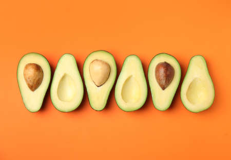 Cut fresh ripe avocados on orange background, flat lay Banque d'images - 129470110
