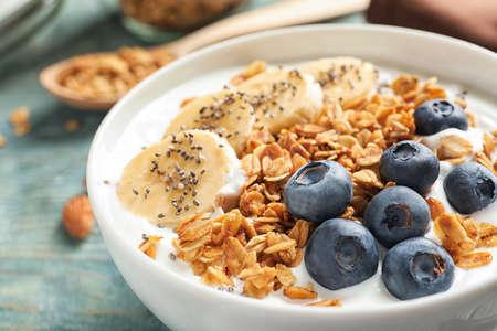 Miska jogurtu z jagodami, bananem i płatkami owsianymi na drewnianym stole, zbliżenie