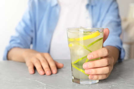 Woman with glass of citrus refreshing drink at grey marble table, closeup Standard-Bild - 129454562