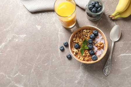 Bowl of tasty oatmeal with blueberries and yogurt on marble table, flat lay. Space for text 写真素材