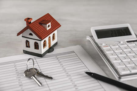 Calculator, house model, keys and documents on light table. Real estate agents workplace