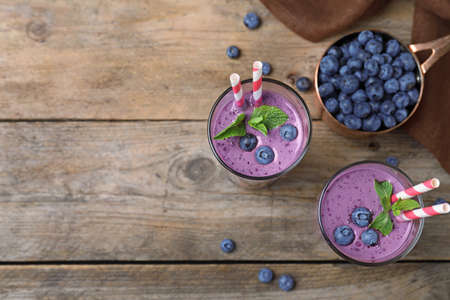 Flat lay composition with delicious blueberry smoothie on wooden background. Space for text