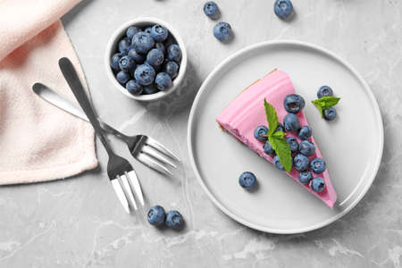 Flat lay composition of tasty blueberry cake on grey table