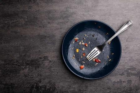 Schmutziger Teller mit Essensresten und Gabel auf grauem Hintergrund, Ansicht von oben. Platz für Text Standard-Bild