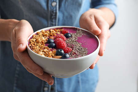 Woman holding bowl of acai smoothie with granola and berries, closeup