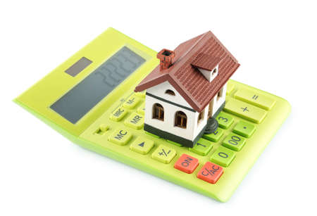 Calculator and house model on white background. Real estate agent concept