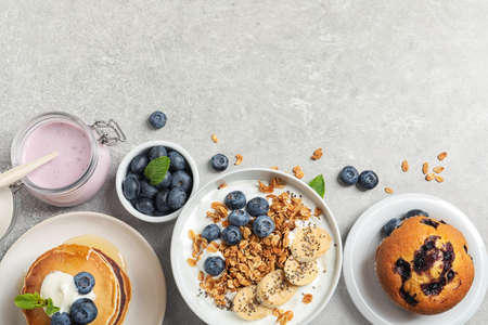 Different tasty dishes with blueberries on grey table, flat lay. Space for text