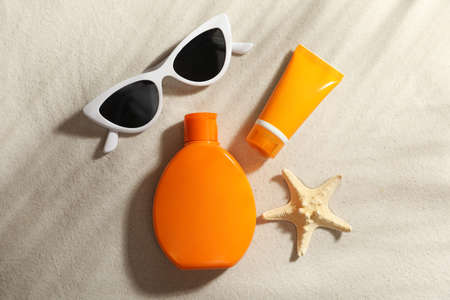 Flat lay composition with sun protection cosmetic products on sand Фото со стока