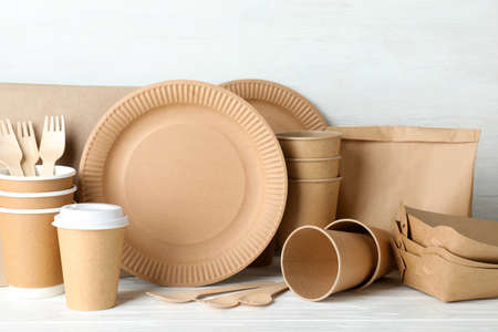 New paper dishware on table against white wooden background. Eco life