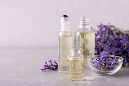 Bottles of essential oil and bowl with lavender flowers on stone table against light background. Space for text Фото со стока