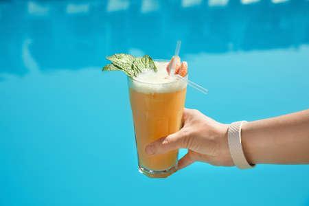 Woman with refreshing cocktail near swimming pool outdoors, closeup Zdjęcie Seryjne