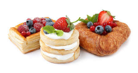 Fresh delicious puff pastries with sweet berries on white background