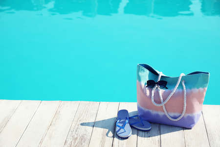 Beach accessories near swimming pool on sunny day. Space for text Zdjęcie Seryjne - 129311608