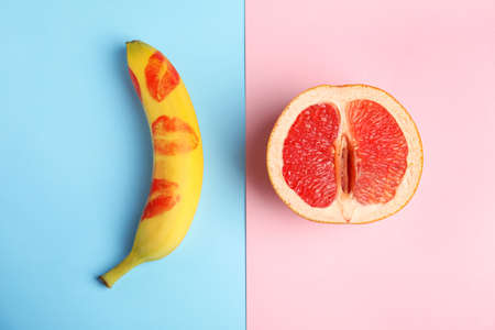 Flat lay composition with fresh banana and grapefruit on color background. Sex concept