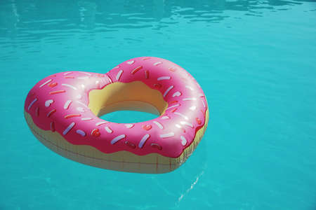 Heart shaped inflatable ring floating in swimming pool on sunny day Zdjęcie Seryjne - 129318833