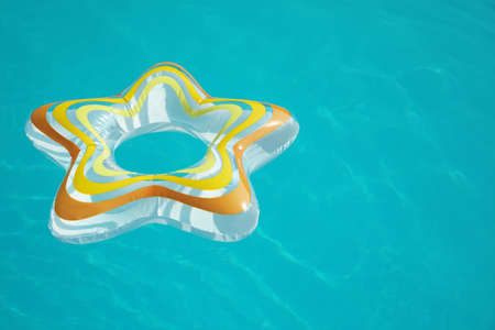 Star shaped inflatable ring floating in swimming pool on sunny day. Space for text Zdjęcie Seryjne - 129318874