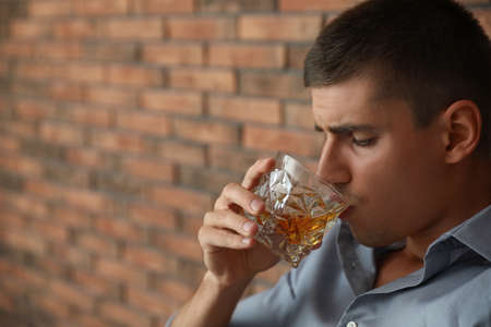 Young man with glass of whiskey near brick wall indoors. Space for text Фото со стока