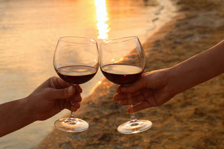 Romantic couple drinking wine together on beach, closeup view