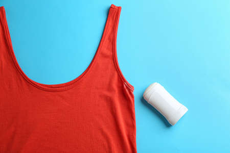 Clothes with stain and deodorant on light blue background, top view