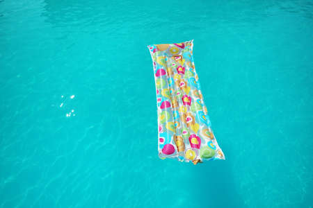 Colorful inflatable mattress floating in swimming pool on sunny day. Space for text