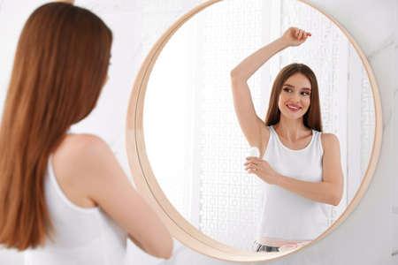 Beautiful young woman applying deodorant in bathroom