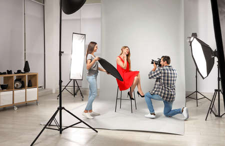 Professional photographer with assistant taking picture of young woman in modern studio Stok Fotoğraf